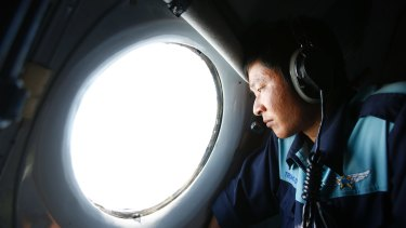 Military officer Nguyen Tran looks out from a Vietnam Air Force aircraft during an earlier mission to find MH370.
