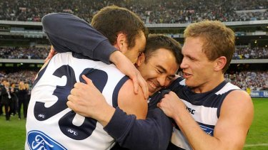 Caught in the middle: Coach Chris Scott gets a hug from Cats Matthew Scarlett (left) and Joel Selwood.