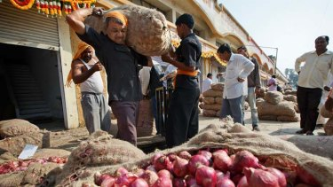 A worker carries a bag of onions at a wholesale market in Nashik, Maharashtra.