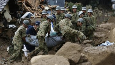 Japanese soldiers and police carry the body of a victim after the landslide swept through a residential area at Asaminami ward in Hiroshima, western Japan.