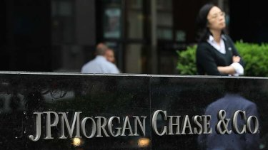 $2 billion trading blunder ... pedestrians walk past a sign outside of a JPMorgan Chase office in New York.
