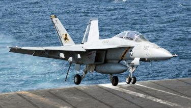 Air cover ... US Navy F/A-18F Super Hornet lands aboard the aircraft carrier USS George H.W. Bush in the Persian Gulf.
