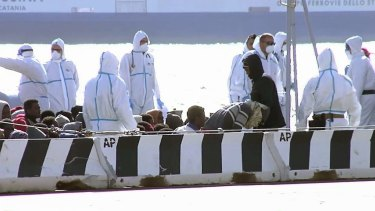 Sitting asylum-seekers, surrounded by emergency relief workers at the Italian port of Messina on Saturday.