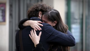 A couple embrace after laying flowers at the La Belle Equipe cafe in Paris.
