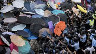Makeshift shield: Protesters hold up umbrellas to try to protect themselves from tear-gas as pro-democracy demonstrators bring parts of central Hong Kong to a standstill.
