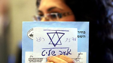 "An Israeli election official holds up an invalid general election ballot with a note glued to it that reads in Hebrew: ""The State of Israel wants Gilad Shalit"", referring to the Israeli soldier captured by Hamas in 2006."