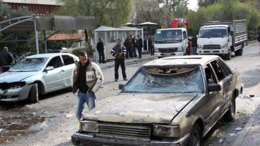 Devastation ... a man inspects a damaged vehicle at the site of a suicide bombing in Damascus on Friday.