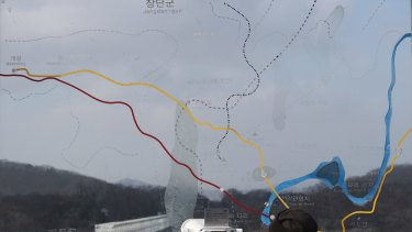 A visitor watches the north side through the glass showing a map of the border area between North and South Koreas at the Imjingak Pavilion in Paju.