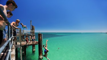 A teengager jumps off the Glenelg jetty during a heat wave in Adelaide in January 2014