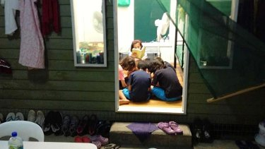 Hot boxes … a family reads together inside one of the wooden dongas.