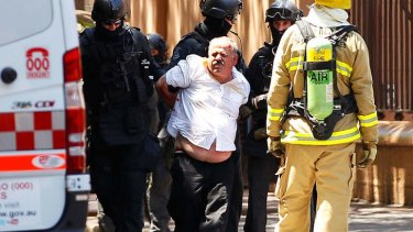Abdula Ganiji is placed under arrest by tactical police outside NSW Parliament House on Maquarie Street.