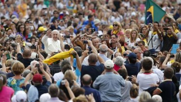 Man of the people: Pope Francis waves as he arrives to lead his Wednesday general audience in St Peter's square at the Vatican.