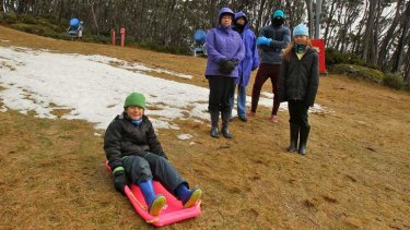 After travelling from Adelaide, Tom Ricci (on toboggan) and his family found most of the snow had melted.