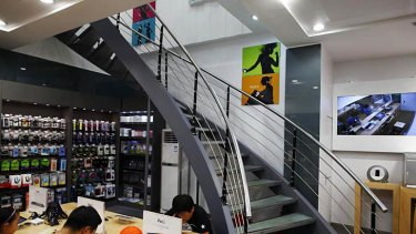 Customers test out electronic products in a fake Apple Store in Kunming, Yunnan province on July 22, 2011.