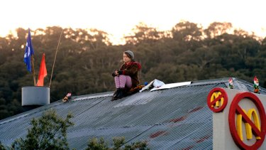 A protester sits on the roof of the proposed McDonald's in Tecoma.