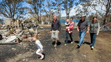 Tammy and Tim Holmes and family at their property near Dunalley on Friday. The family had to shelter underneath a small jetty with their grandchildren to escape from the recent bushfire on Tasmania's east coast.