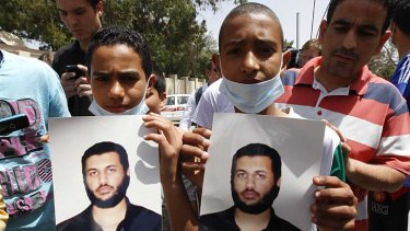 Young men hold pictures of Saif al-Arab Gaddafi.