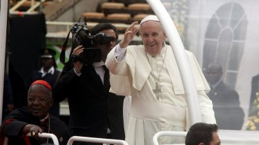 Pope Francis waves as he arrives for a meeting with youths at Kasarani Stadium, in Nairobi.