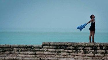 Wave goodbye ... a Kiribati local on one of the failing sea walls.