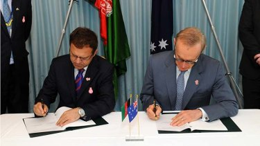 Agreement ... Omar Zakhilwal and Bob Carr sign in Tokyo.