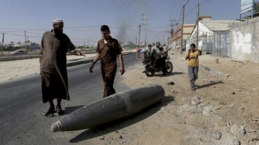 Pedestrians inspect an Israeli fighter jet external fuel tank, known as drop tank, on a main road in Deir al-Balah, central Gaza.