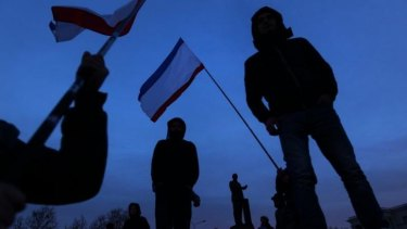 People celebrate the preliminary results of the Crimean referendum at dusk in Lenin Square.