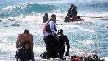 A man rescues a migrant from the Aegean, Monday, April 20.