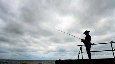 Khodar Assaad fishes off Altona Pier under grey skies.