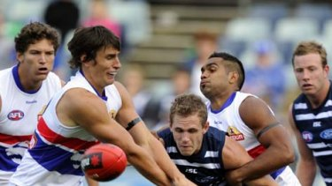 Joel Selwood gets in a tangle with Bulldogs Ryan Griffen and Nathan Djerkurra.