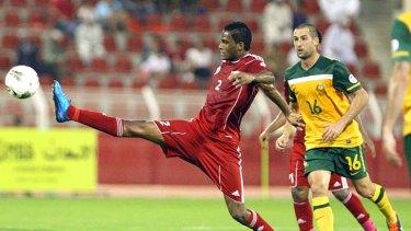 Omani player Eid al-Farsi takes control watched by Socceroo Carl Valeri.