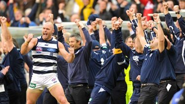 It's ours: The Geelong bench, with Josh Hunt at the front, stands and cheers at the final siren.