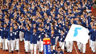 Athletes from North and South Korea march together, led by a unification flag during opening ceremonies for the 14th Asian Games in Busan, South Korea in 2002 when they conducted a joint march during the opening and closing ceremonies.