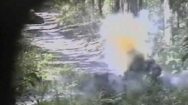 """Big, bad bombs"" ... this still shows a bomb exploding in bushland after an undercover officer shows Abdul Benbrika how to detonate it."