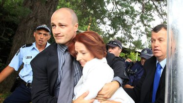 Prime Minister Julia Gillard is dragged to safety amid the protests on Australia Day.
