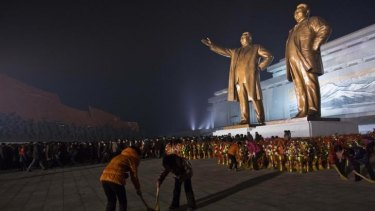 North Koreans pay their respects at the base of statues of the late leaders Kim Il Sung and Kim Jong Il, in Pyongyang, North Korea.
