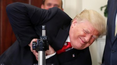 US President Donald Trump tries unsuccessfully to crush a Corning glass sample during an event in the White House on Thursday.