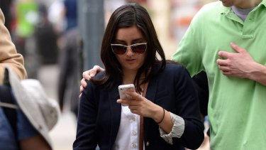 A woman uses her smartphone as crossing street in Washington.