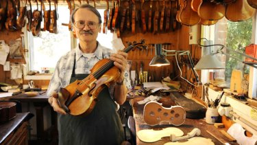 John Ferwerda holds a violin once owned by the late concert master Leonard Dommett. The  instrument, made in 1727, is valued at more than $100,000.