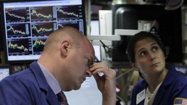 Wall Street tumbles ... traders at the New York Stock Exchange.