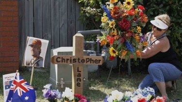 An Oklahoma resident places flowers at a memorial at the scene where Australian college student Christopher Lane was killed.