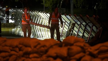 Members of the military construct a new levee after initial attempts failed.
