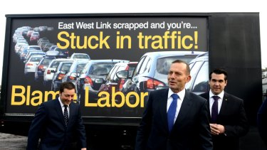 """Prime Minister Tony Abbott, flanked by Victorian Opposition Leader Matthew Guy, left, and local member Michael Sukkar, stand in front of a """"Blame Labor"""" sign."""
