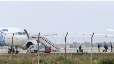 Passengers or crew members leave the hijacked aircraft of Egyptair at Larnaca airport.