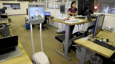 Senior software engineer, Josh Faust, seen on screen, navigates his company's office using a Beam remote presence system, as fellow engineer Stephanie Lee, at right, works on a project at Suitable Technologies in Palo Alto, California.