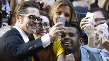 Brad Pitt spends some time taking selfies with fans at the Unbroken premiere in Sydney.