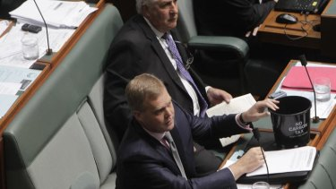 Liberal backbencher Tony Smith with a plastic pot during question time.
