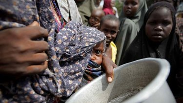A woman holding her young child while queuing for food at Badbaado, a new camp established by the Transitional Federal Government for internally displaced people, Somalia.