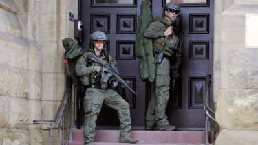 Armed officers on guard on Parliament Hill after the attack.