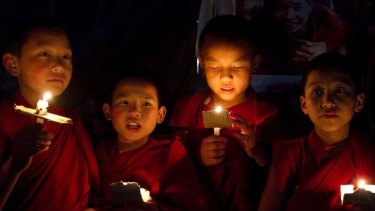 Novice monks hold a candlelight vigil to protest against violence by Chinese police against Tibetan demonstrators.