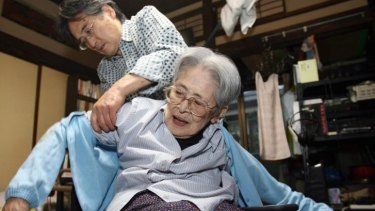 Hiromichi Takeuchi helps his 93-year-old mother Iyo. Japan is to look at robotics to assist look after its ageing population.